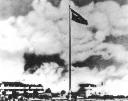 Hickam Field barracks burning. The American flag is ripped and tattered, but still flying. That same flag flew over the White House on 14 Aug. 1945 when the Empire of Japan accepted surrender terms.