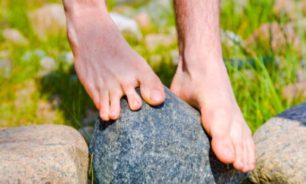 bare-feet-balancing-on-rock